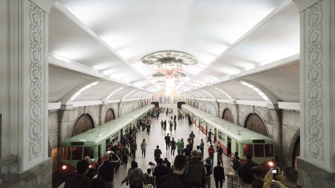 Historical style metro station buzzing with passengers and metro waiting on each tracked